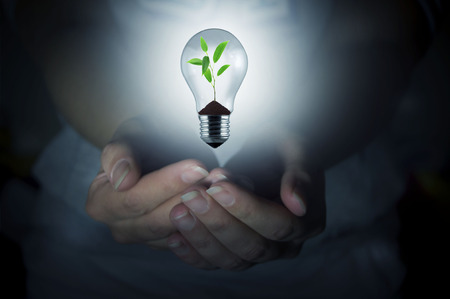 hands holding a light bulb turned on blurred background Stock Photo