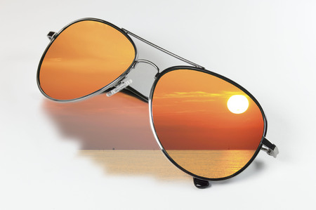 sunglasses that reflect the sky at sunset on a white background