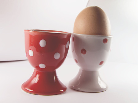egg in white egg cup on white background with overexposed lights