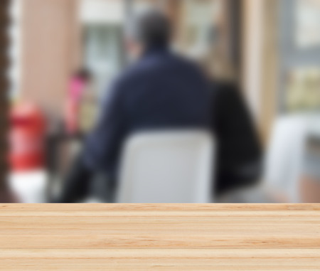 second floor: blurred background with people sitting at the bar and wooden table in the foreground