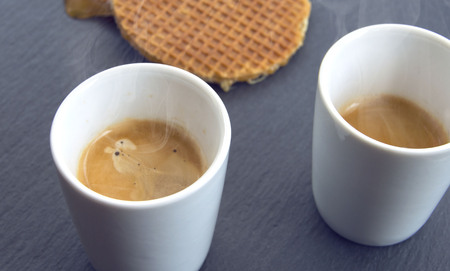 Two cups of coffee with honey wafers on a stone surface