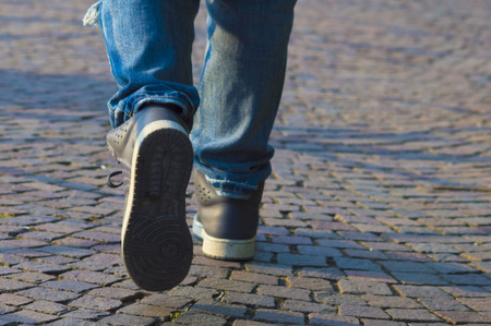 migrate: person walking with sneakers and jeans on city street Stock Photo