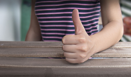 hooray: person giving the thumbs-up on blurred background