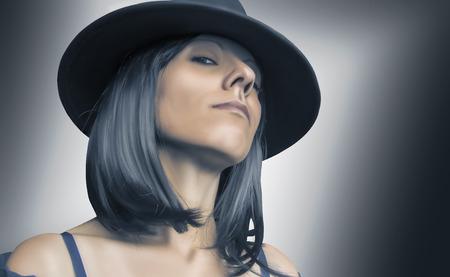 Gangster vrouw met hoed en zwart haar op wazige achtergrond