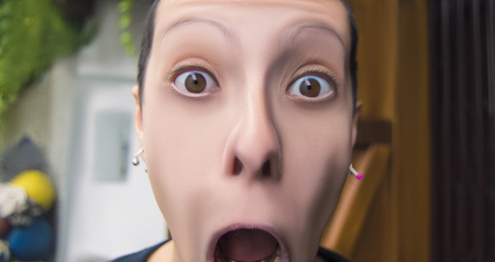 hallucinations: frightened woman screaming with mouth wide open on blurred background