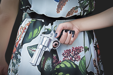 woman seen from behind with the gun in his hand on a black background
