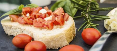 in particular: Garlic bread bruschetta with cherry tomatoes and ingredients on a black stone dish Stock Photo