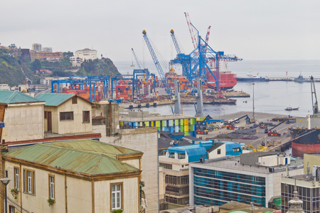 Boat docked on Valparaiso port. Valparaiso buildings are shown in foreground. Foggy day. Stock Photo