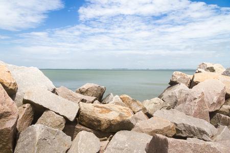 breakwater: rocks of cassino breakwater with beach in background