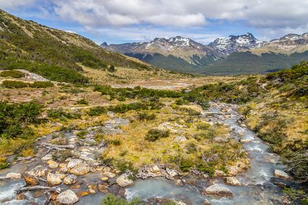 Stream in Laguna Esmeralda trail with  mountains and vegetation, Ushuaia, Patagonia, Argentina Stock Photo
