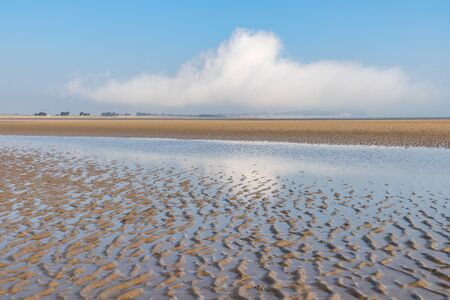 Clouds and sand with reflection in Burrow beach, Sutton, Dublin, Ireland 写真素材