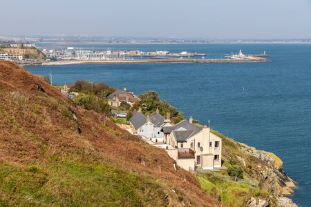 Houses in cliff with Howth Pier in background, Howth, Dublin, Ireland Stock Photo