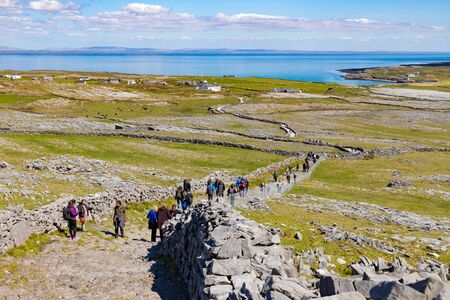 Rock wall, farms, tourists and Galway bay in Inishmore, Aran Islands, Ireland