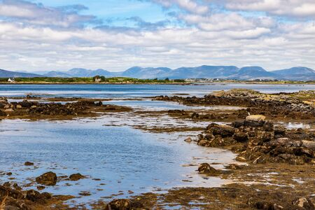 Bay with low tide, seaweeds and mountains in Carraroe, Conemara, Galway, Ireland