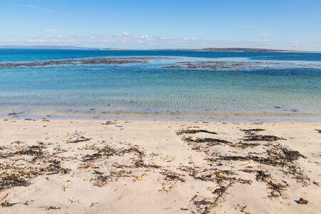 Beach with sand, rocks and seaweeds in Inishmore, Aran Islands, Ireland