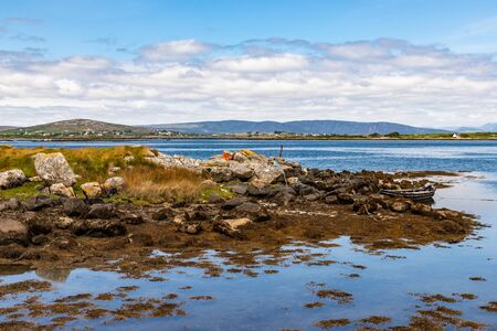 Bay with low tide, seaweeds, boat and mountains in Carraroe, Conemara, Galway, Ireland