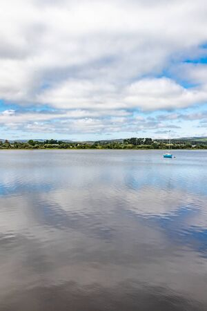 Boat in Lough Corrib with forest and farm fields in background, Oughterard, Ireland