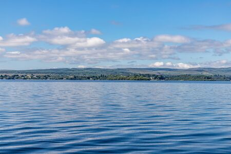 Lough Corrib with forest and farm fields in background, Oughterard, Ireland