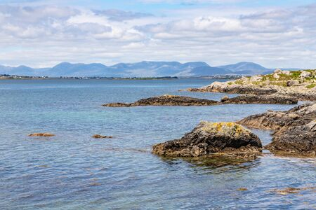 Beach with rocks and mountains in Carraroe, Conemara, Galway, Ireland