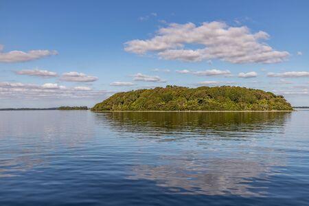 Island, Clouds and reflections in Lough Corrib lake, Cong, Mayo, Ireland