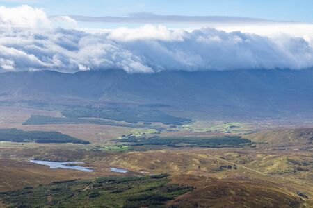 Nuvole che coprono la montagna e la valle con campi e foreste presi da Croagh Patrick mountain, Westport, Ireland Archivio Fotografico