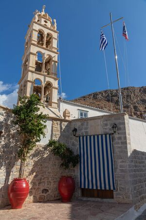 Church with tower and flags in Hydra Island, Greece