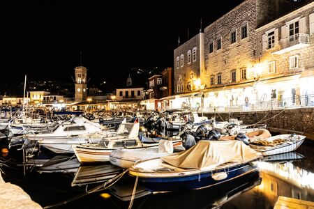 Night lights of Boats and buildings around pier in Hydra Island, Greece