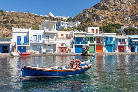 Boat Coloured houses in Klima beach with Trypiti village in background, Milos, Greece