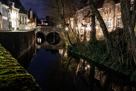 Light night with buildings with reflections around channels in Bruges, Belgium