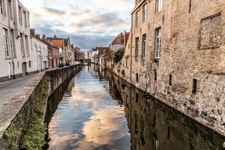 Buildings around channels in Bruges at sunset, Belgium