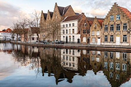 Buildings with reflections around channels in Bruges at sunset, Belgium