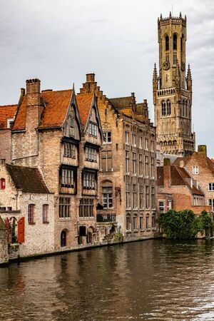 Buildings around channels and clock tower in Bruges, Belgium