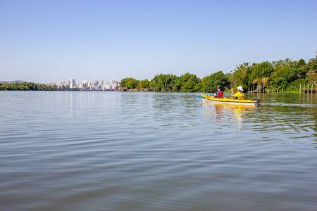 Paddling in Guaiba river and Buildings in Porto Alegre city in background, Rio Grande do Sul, Brazil