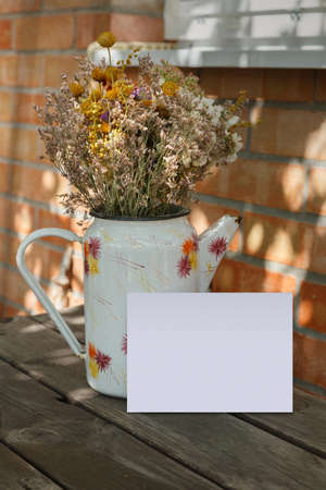 Postcard mockup with old enameled jug and dried flowers. Empty card with space for text, print or lettering. Vintage wooden table and brick wall. Atmospheric moments.