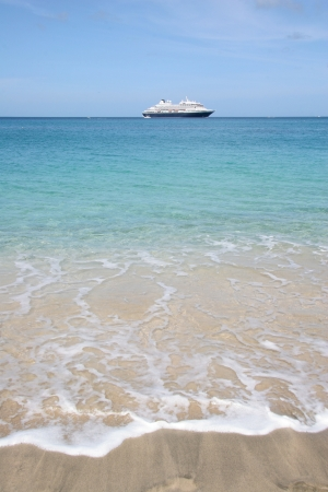 Cruise ship on the horizon of beautiful tropical beach photo