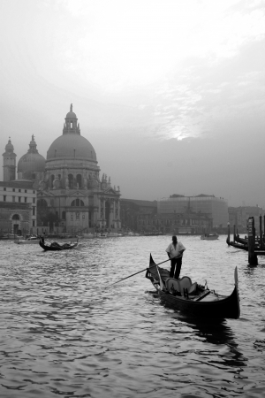 Black   white image of a gondollier punting across the water along the Grand Canal, Venice, Italy