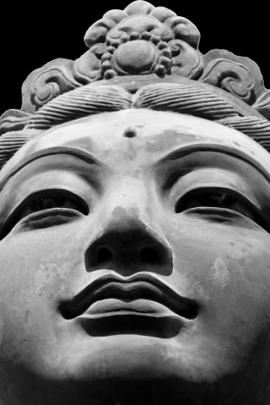 stone buddha: Black   White close up of one of the six  The Offering of the Six Devas  statues which are surrounding the Tian Tan Big Buddha in Hong Kong  Stock Photo