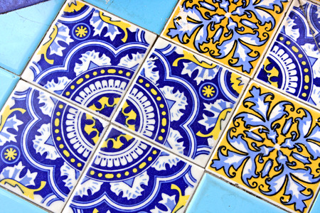 Close up of traditional Spanish ornate ceramic wall tiles  Multi coloured with pale   dark blues   yellow