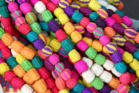Hand made brightly coloured necklace made with woven straw, South America   Stock Photo