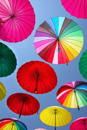 rainbow umbrella: Collection of multi colored umbrellas hanging up in an open position over a street offering shade & protection from the elements.