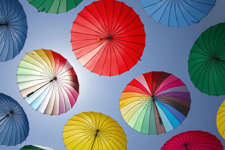 Collection of multi colored umbrellas hanging up in an open position over a street offering shade & protection from the elements.