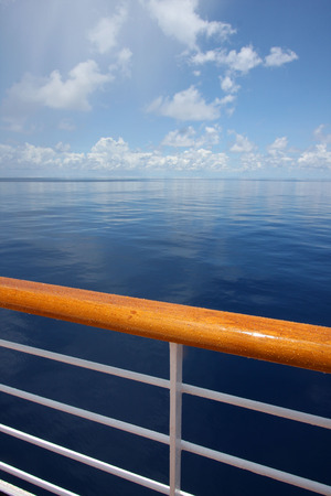 hand rail: View of a calm still ocean on a beautiful sunny day, with the hand rail of a criuse ship in the foreground.