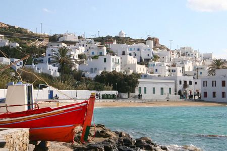 Mykonos town on a beautiful sunny day. All the buildings are painted white & many have traditional blue doors & windows. A traditional red fishing boat is in the foreground, Mykonos, Cyclades, Greece. photo
