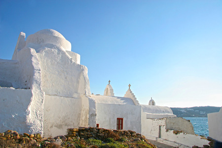 mykonos: Traditional whitewashed church close to the waters edge of the Agean sea, Mykonos town, Cyclades, Greece. Stock Photo
