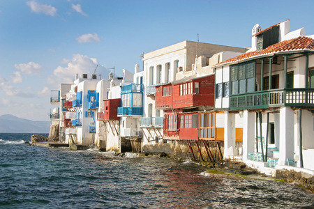Traditional whitewashed buildings built on the edge of the coastline with the Agean sea below, Mykonos town, Cyclades, Greece. photo