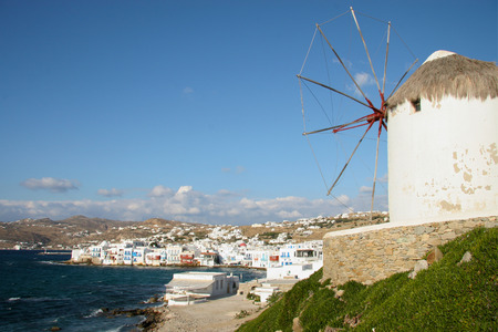 traditinal: Traditinal windmill on the hillside with whitewashed homes in the background. The harbour & coastline can be seen below, Mykonos town, Cyclades, Greece. Stock Photo