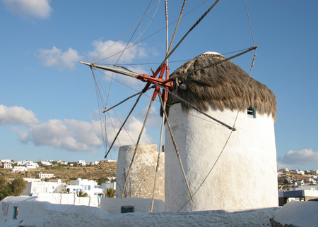 traditinal: Traditinal windmill on the hillside with whitewashed homes in the background, Mykonos town, Cyclades, Greece. Stock Photo