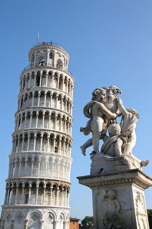 cherubs: Leaning tower of Pisa with the Statue of cherubs or (La Fontana Dei Putti Statue), Piazza dei Miracoli, Pisa, Tuscany, Italy. Stock Photo
