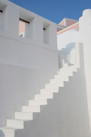 upstairs: Minimal white stone staircase between two white walls with rooftops above, Oia, Santorini, Greece.