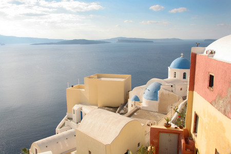 Traditional white church with a Blue dome, perched on the side of the cliff, Oia, Santorini, Greece. photo
